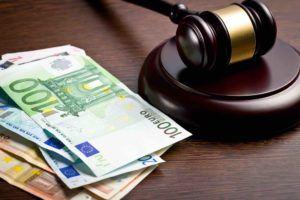 Euroscheine liegen neben Gerichtshammer