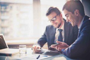 2 Männer im Anzug besprechen sich im Büro
