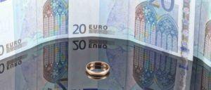 Ehering liegt auf einem Tisch vor Geldscheinen