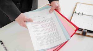 Ein Mann hält verschiedene Dokumente in Händen