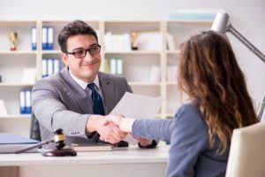 Anwalt und Mandantin schütteln sich die Hand