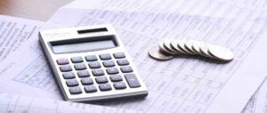 Taschenrechner und Münzen liegen auf Unterlagen