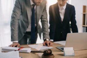 Zwei Geschäftspartner besprechen an einem Schreibtisch das GmbHG Gesetz