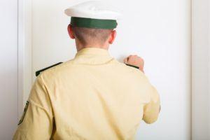 Polizist klopft an Tür