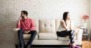 Mann und Frau sitzen auf dem Sofa und drehen sich den Rücken zu