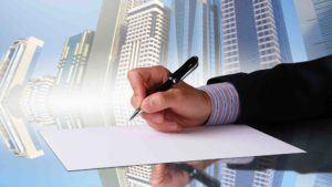 Hand mit Stift setzt zur Unterschrift an, im Hintergrund Hochhäuser