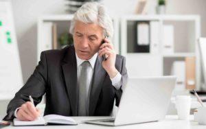 Mann sitzt am Schreibtisch, telefoniert