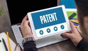 Tabletscreen zeigt das Wort Patent gehalten von einem Mann am Schreibtisch