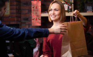 Verkäuferin gibt Mann Tüte im Geschäft