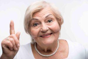 Ältere Dame zeigt mit Zeigefinger auf.