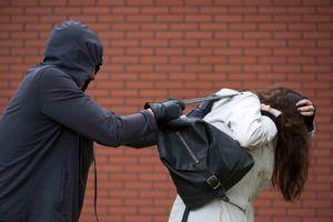 Maskierter greift nach einer Handtasche