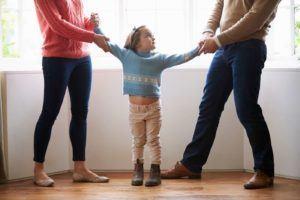Eltern halten das Kind an den Armen fest