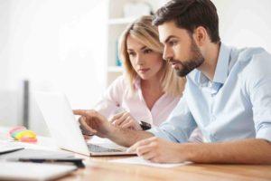 Ehepaar begutachtet am Laptop offene Rechnungen
