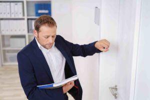 Geschäftsmann klopft an Tür und hat Sanierungsverfahren