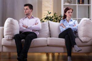 Ehepaar sitzt weit voneinande entfernt auf einer Couch