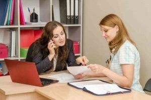 Zwei Frauen diskutieren beim Schreibtisch