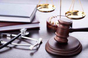 Medizingerät und Gerichtshammer am Tisch