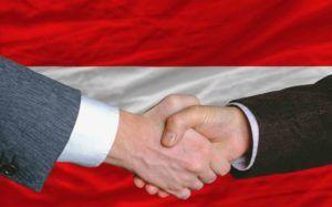 Hände schütteln vor österreichischer Fahne