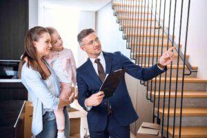 Makler zeigt junger Mutter eine Wohnung
