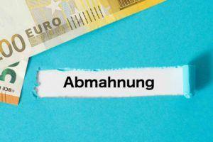 Das Wort Abmahnung mit Geldscheinen