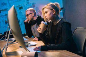 Mitarbeiterin und Mitarbeiter sitzen vorm Computer und Arbeiten
