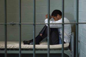 Mann sitzt im Haft hinter Gittern und wird eine Ersatzfreiheitsstrafe abgeleistet