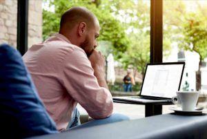 Mann sitzt vor Computer und löscht Google-Einträge