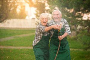 Älteres Ehepaar hat Spaß beim Gießen am Hof