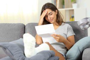 Junge Frau mit gebrochenem Bein liest ihre Kündigung