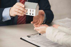 Haus wird in eine Damenhand gelegt als Symbol für Mietvertrag