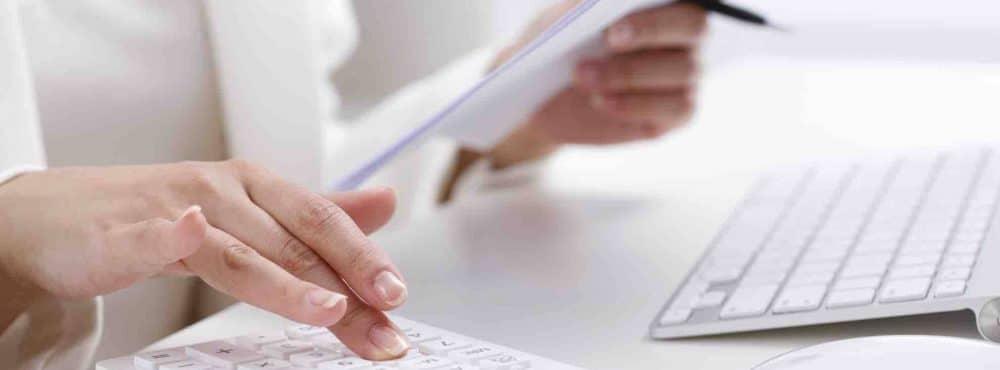 Frau sitzt am Schreibtisch und tippt in Taschenrechner
