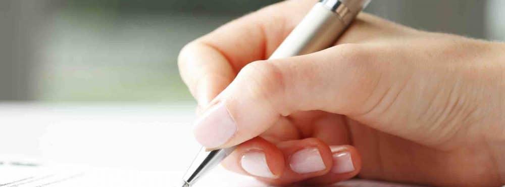 Frauenhand hält Stift und füllt Formular aus