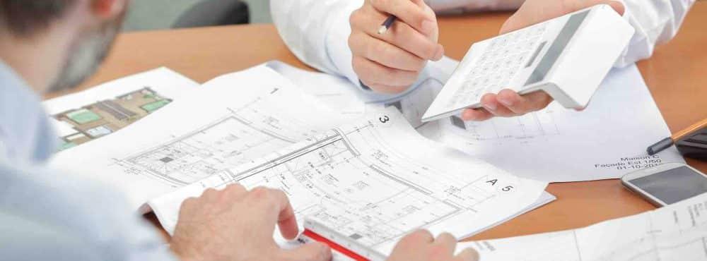 zwei Männer am Tisch, Baupläne, Taschenrechner