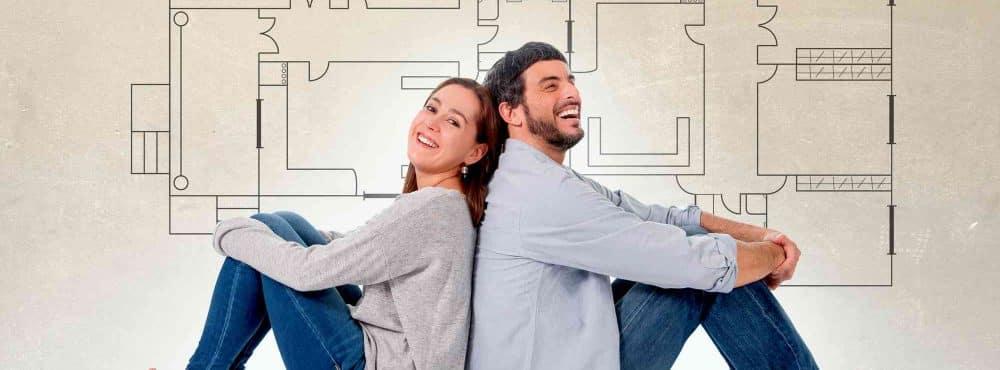 Ehepaar mit Bauplan im Hintergrund
