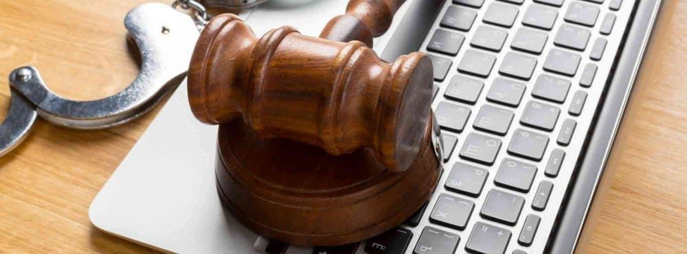 PC mit Handschellen und Anwaltshammer
