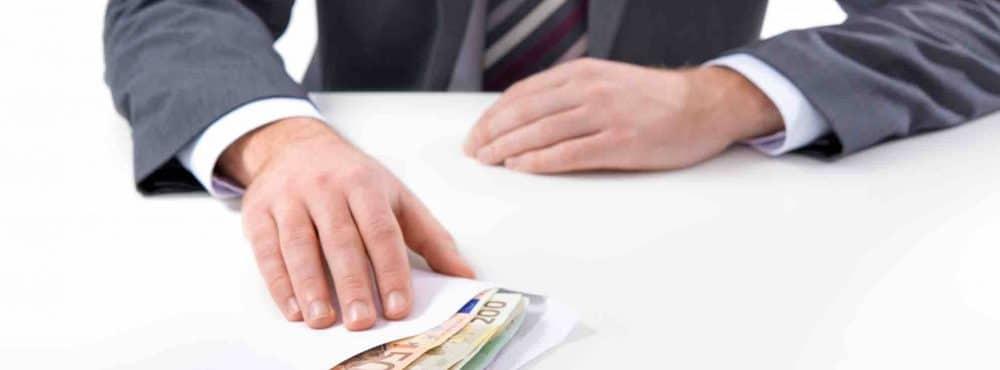 Mann schiebt Umschlag mit Geld über den Tisch