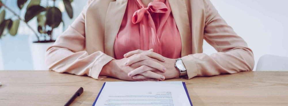 Geschäftsfrau sitzt vor Vertrag