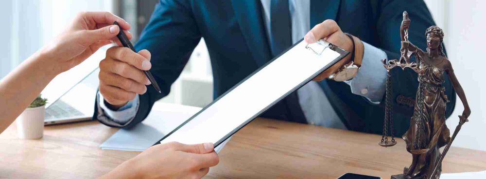 Frau unterzeichnet beim Anwalt einen Vertrag