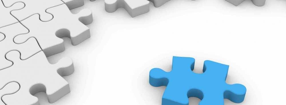 weiße Puzzleteile und ein blaues Puzzleteil