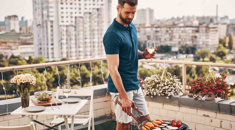 Mann grillt am Balkon