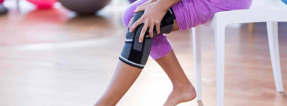 Frau trägt aufgrund einer Körperverletzung eine Knieschiene