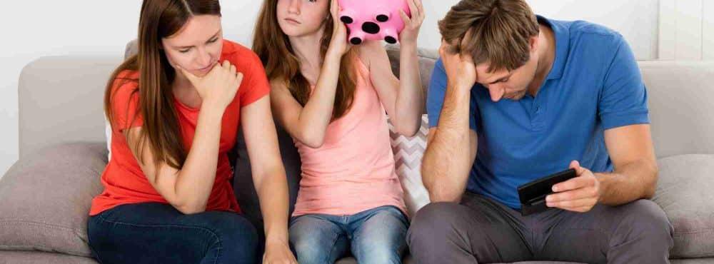 Kind sitzt zwischen Elternteilen mit Sparschwein in der Hand