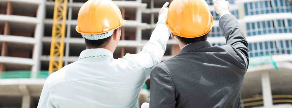 Zwei Männer zeigen auf Baustelle
