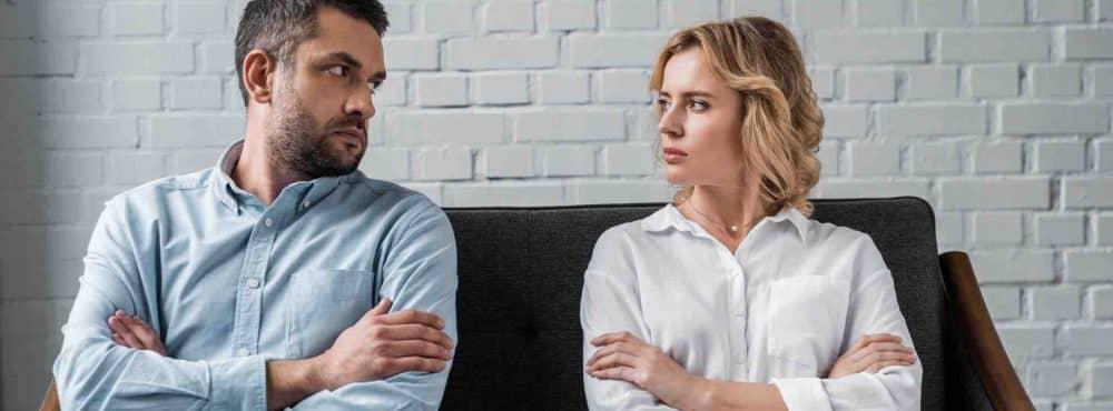 Paar sitzt mit verschränkten Armen auf dem Sofa und schaut sich böse an