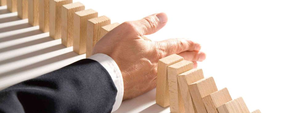 Hand stoppt Holzsteine. Symbol für Umgründung