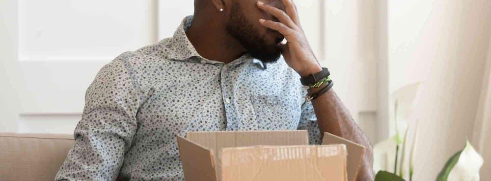 Afrikaner sitzt gestresst, Ware im Karton kaputt