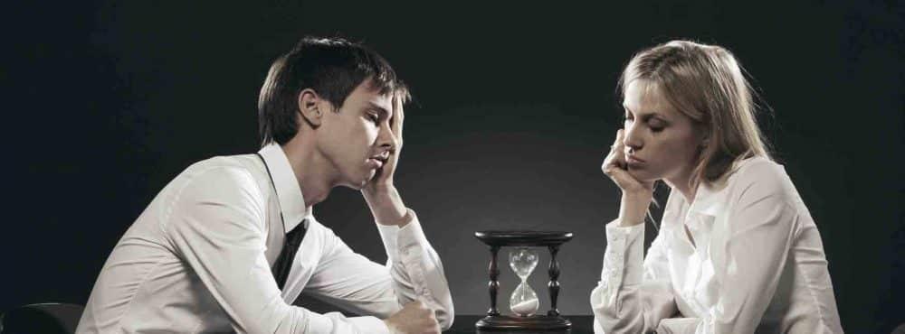 Unglückliches Paar starrt auf eine Sanduhr